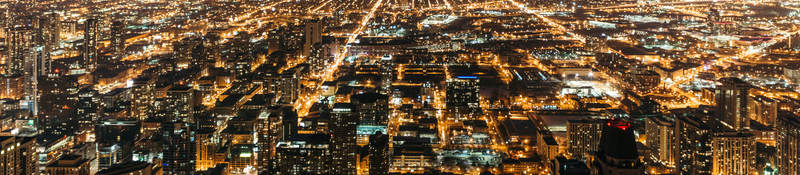 Cityscape at night with many lights from homes, businesses, roads
