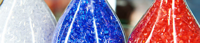 Colorful plastic granular polymer in glass flasks