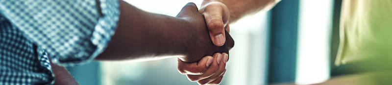 A black man and white man shaking hands