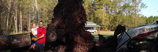 Jeremy Tyndall and his daughter pose before Hurricane Florence debris,