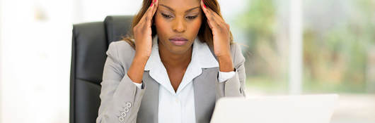 Stressed businesswoman sitting in office rubbing her head