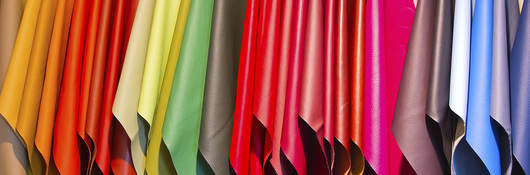 A variety of different colored fabrics hang on a rack.