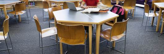 A girl reading a book at a table in the library.