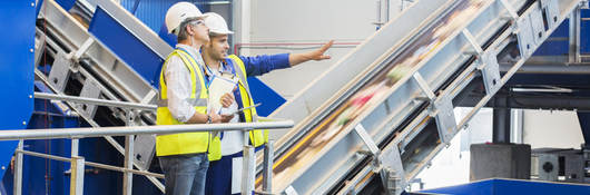 Two workers in a recycling facility stand next to moving conveyor belts.