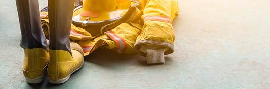 A yellow fireman's uniform and boots laying on the ground.
