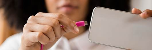 A person plugging a cord into a handheld device