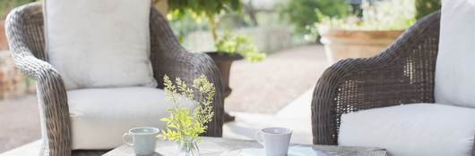 An vignette of two brown wicker chairs solidly resting on an outdoor patio.