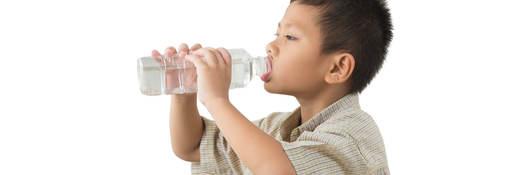 A boy drinking from a water bottle.