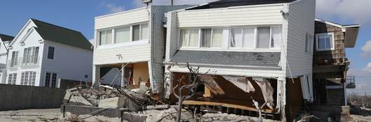 A white clad destroyed beach house four months after Hurricane Sandy.