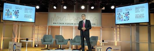 Tom Chapin, Ph.D, standing onstage with the 2019 Pritzker Forum on Global Cities banner in the center and two monitors showing the average number of batteries on any one person at any given time, to the left and right. Tom is wearing a blue suit with a red tie.