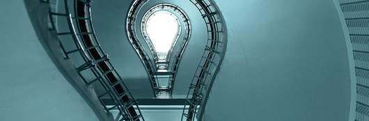 A light bulb sits at the bottom of a circular staircase.