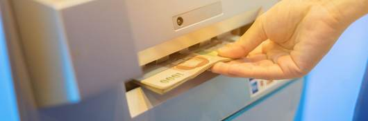 Hand accepts money dispensed from ATM machine