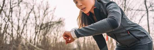 A female runner checks her time on her smart watch. She's wearing black on black performance material workout gear.