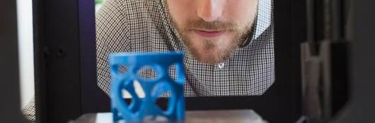 Man looks at a blue gadget made with additive manufacturing
