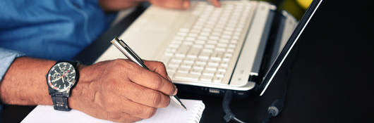 Close-up of a man's hands, ready to take notes while following training on his laptop