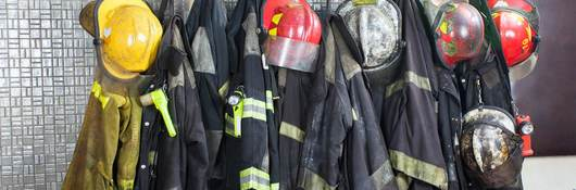 Firefighter gear hangs in a row, waiting for the next call