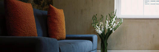 Photo of a blue couch with orange throw pillows