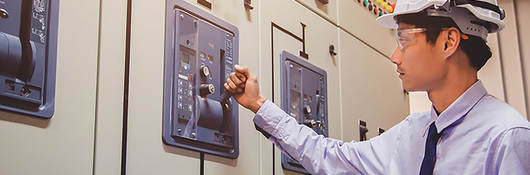 An engineer is checking voltage or current by voltmeter in control panel of power plant