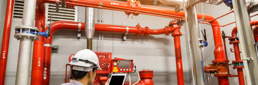 Engineer with tablet checks red generator pump for water sprinkler piping and fire alarm control system.