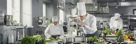 foodservice professionals (chefs) in a high-end commercial kitchen
