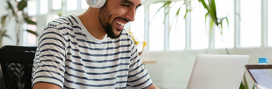 Man listening to headphones while working on laptop