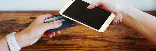 chip-enabled credit card in touching a cellphone