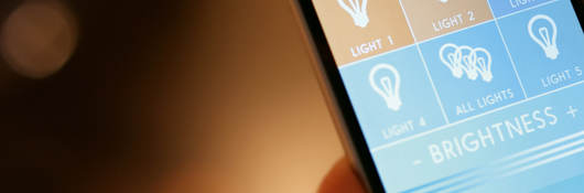 Person's hand holding phone that controls lights in a house