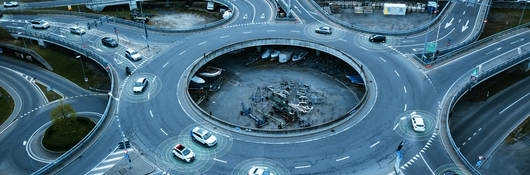 Autonomous self-driving cars moving in a traffic circle next to a highway.