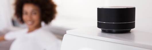Close up of smart speaker with woman in blurred background