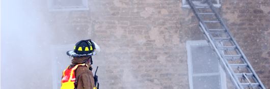 firefighter with radio at burning building