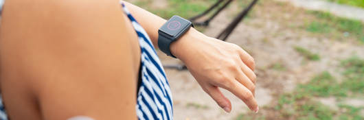Young woman with wearable patch on arm checking a smartwatch to see her blood sugar level.