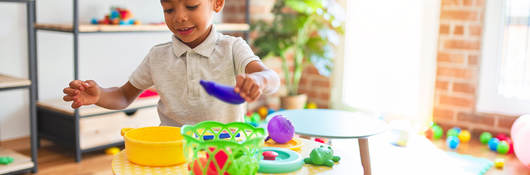 Child playing with plastic food and cutlery toys