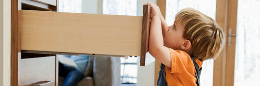 A child pulling on an open dresser drawer, a furniture tip-over risk