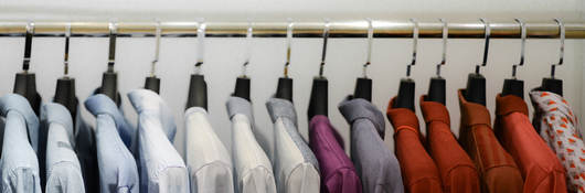 Close-Up Of Colorful Clothes Hanging On Rack At Store