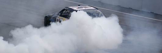 Race car drifting with smoke behind it