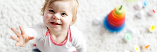 Smiling child surrounded by toys.