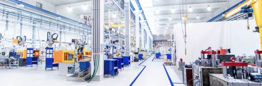 warehouse with clean white floor, machinery and bright commercial lighting