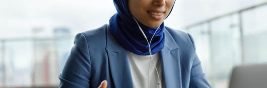 A young woman gestures while using a laptop.