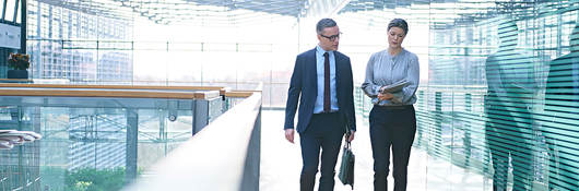 Two employees having a walking meeting in a glass building