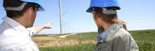 Technicians in blue hard hats standing in a field with an iPad while pointing at wind turbines