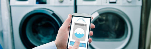 A homeowner demonstrates how connected products work as he operates the washing machine with his phone.