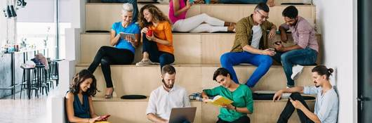 Group of young adults sitting on indoor tiered seating using their mobile phones and tablets.