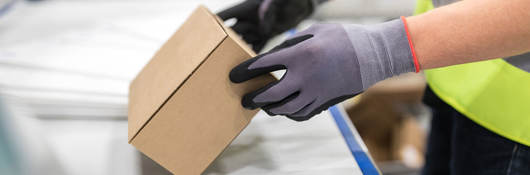 Worker checking package from conveyor belt in warehouse