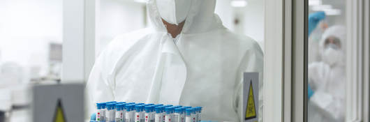 Person in PPE carrying tray of test tubes