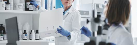 Gray-haired female scientist holding binder in lab