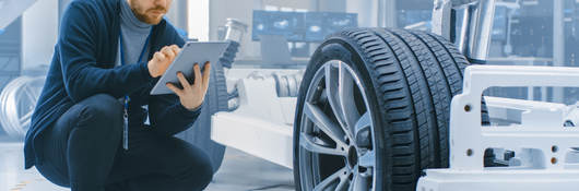 Engineer in an automotive laboratory works on a tablet and evaluates a car prototype