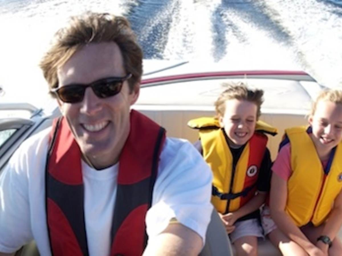 Family of three smiling, boating and wearing life jackets.