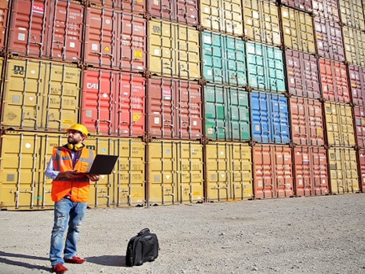 |man standing in front of multiple cargo containers