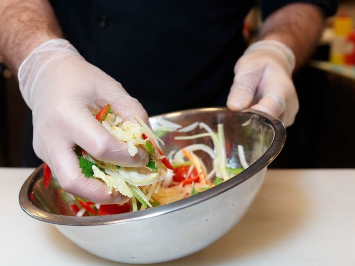 Chef wearing gloves is preparing a salad according to food safety guidelines