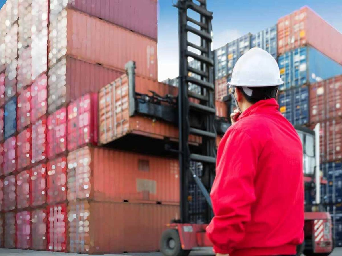 Dock workers supervising cargo container movement,
